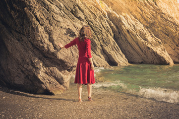 Woman in red dress walking on the beach