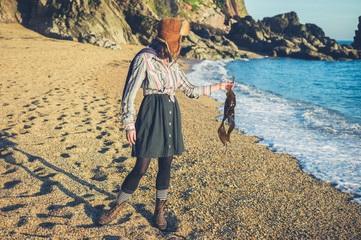 Young woman standing on beach with seaweed in her hand