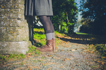 Legs of young woman in the countryside by wall