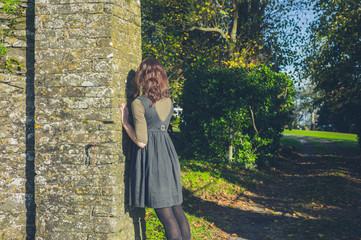 Young woman leaning against stone wall
