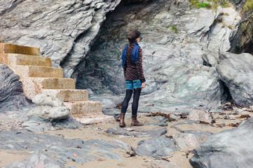 Young woman standing by concrete steps and cliff