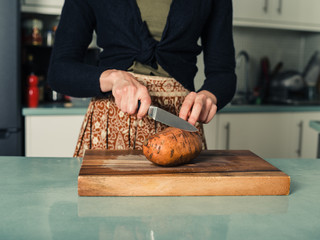 Young woman cutting sweet potato