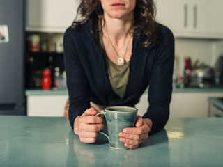 Young woman drinking coffee in kitchen