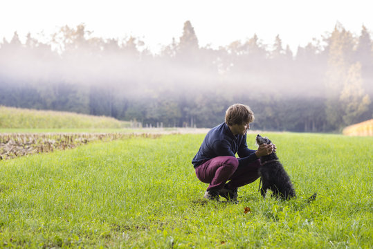 Young man crouching to pet his black dog in a beautiful green me