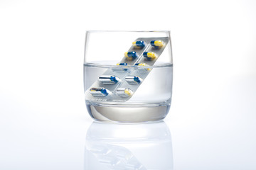 blister of pills in a glass of water