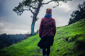 Young woman hiking on hill by tree