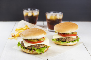 Two mini burgers with meat, lettuce, tomatoes, cheese, pickles,