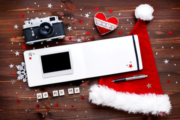 Christmas and New Year background with old fashioned camera, red Santa's hat. notepad and photo.