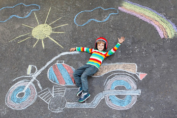 Little kid boy in helmet with motorcycle chalks picture