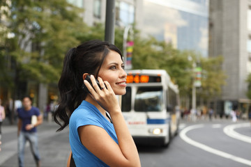 Profile of a smiling woman on her cellphone with a bus pulling up in the background.