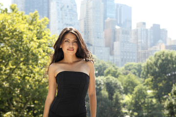 An attractive woman stands on an overlook in Central Park in the sun.