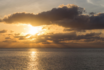 beautiful sunset over the sea with the sun rays through the clou