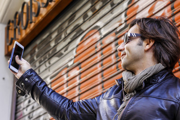 Man in sunglasses making selfie