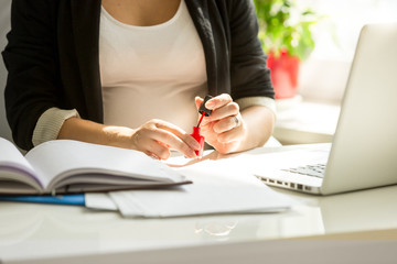 Closeup of businesswoman painting fingernails at office table