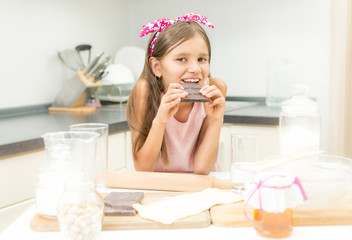 Portrait of girl leaning on kitchen table and eating chocolate