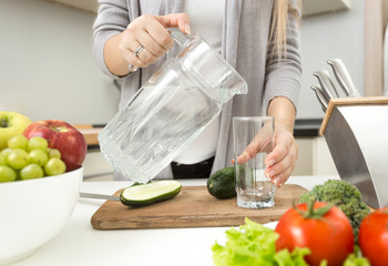 Closeup of woman pouring water in glass on kitchen