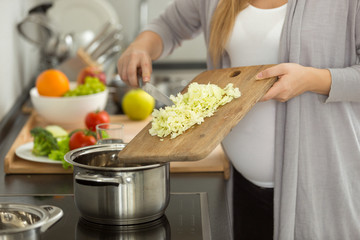 Closeup of pregnant woman cooking vegetable soup