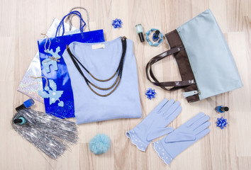 Winter Christmas sweater with accessories arranged on the floor. Woman blue outfit with matching bag, gloves and necklace lied down.