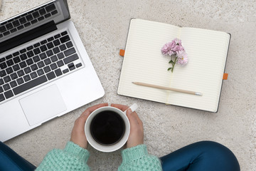 Laptop, notebook and a cup of coffee in girl's hands sitting on white carpet