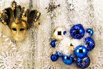 New year theme: Christmas tree white and silver decorations, blue balls, snow, snowflakes, serpentine and golden mask on white retro stylized wood background with yellow backlight
