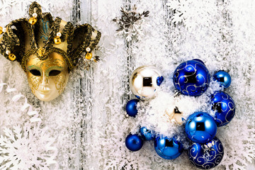 New year theme: Christmas tree white and silver decorations, blue balls, snow, snowflakes, serpentine and golden mask on white retro stylized wood background contrasted