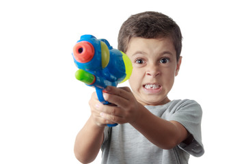 Little boy with funny expression playing with plastic water gun