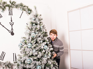 young man standing behind a Christmas tree