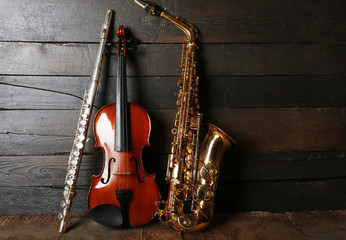 Musical instruments: saxophone, violin and flute on wooden background
