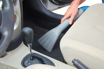 Closeup of a man vacuuming a car interior in the process of detailing an automobile