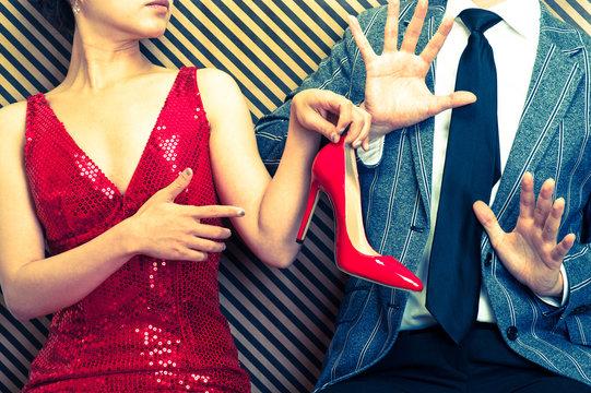 赤いハイヒールを持っている女性と驚いている男性