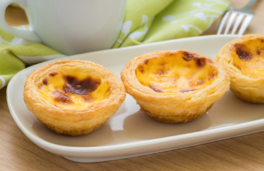 Egg tart on plate and tea cup