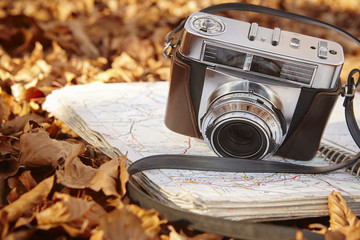 Still life in the autumn forest with camera and map