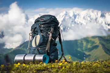 Tourist backpack and sleeping pad on a background of mountains Wall mural