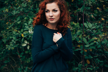 Beautiful young woman with bright red hair posing outdoors