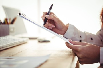 Cropped image of woman writing on clipboard