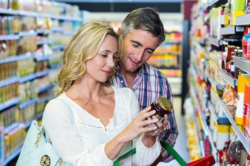 Couple reading nutritional values of food