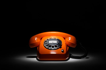 orange retro phone in spotlight on black background