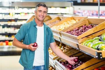 Smiling man choosing a onion