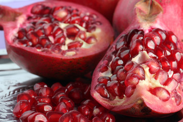 very juicy and big and delicious pomegranate in the section in the tray isolated on purple background