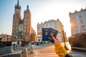 Autocollant pour porte Cracovie Female hands holding Ukrainian abroad passports on the Krakow city center background
