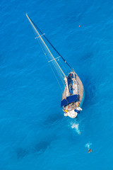 White luxury yacht against azure sea with swimming people