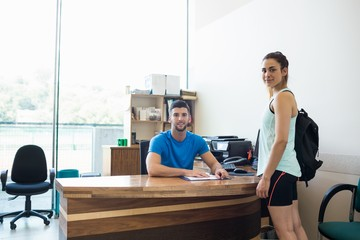 Athletic woman talking with fitness trainer