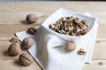 Walnuts in a old white bowl on a wooden background