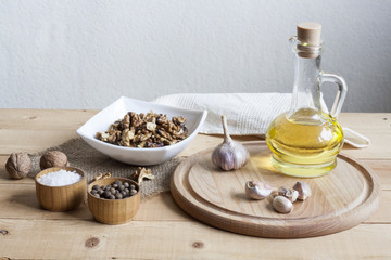 Walnuts in a white bowl, garlic, pepper salt and oil on a wooden background, wooden board and white napkin