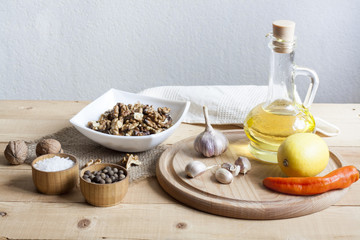 Food ingredients. Oil, eggs, garlic, limon, walnuts and herbs on wooden table. Wooden board and napkin.