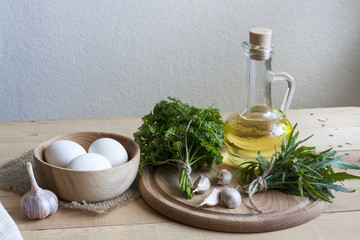 Food ingredients. Oil, eggs, garlic and herbs on wooden table. Wooden board and napkin.