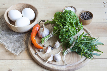 Food ingredients. Eggs, garlic and herbs on wooden table. Wooden board and napkin.