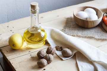 Food ingredients. Oil, eggs, garlic, limon and walnuts on wooden table. Wooden board and napkin.