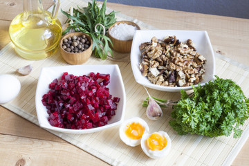 Ingredients for making salad with beets and walnut. The cut products in plates, salt, pepper, herbs, boiled eggs and oil on a wooden table.