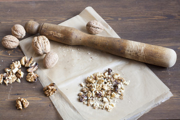 Walnuts in paper and wood battledore on a wooden background